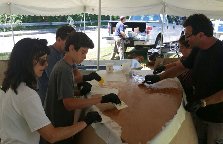Families fiberglass the boat bottom.